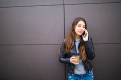 Smiling woman talking on the phone with cup of coffee over wall background Stock Images