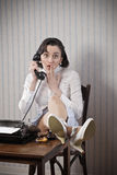 Woman talking on phone at desk royalty free stock photography