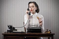 Woman talking on phone at desk Stock Photos