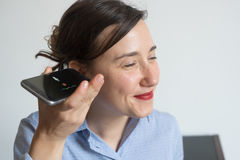 Woman talking on the phone with digital voice assistant. Woman talking on the phone with the digital voice assistant royalty free stock photo