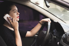 Woman talking on the phone while driving a car Stock Image