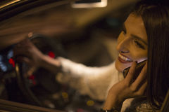 Woman talking on a phone while driving a car Stock Photo