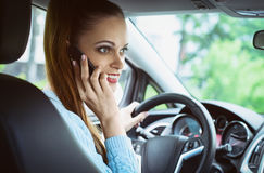 Woman is talking on a phone while driving a car Stock Photos