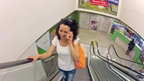 Woman talking on phone on escalator in a mall stock video