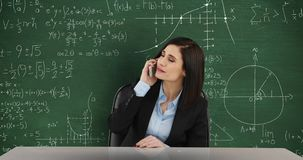Woman talking on phone in front of chalkboard with moving math calculations 4k