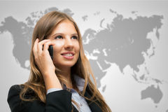 Woman talking on the phone in front of a world map Stock Photo