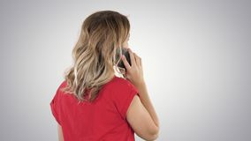 Woman talking on the phone on gradient background. stock footage