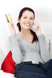 Woman talking on the phone, holding a credit card. Stock Photo