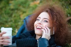 Woman talking on the phone and holding cup with coffee Royalty Free Stock Photography