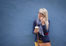 Woman talking on phone and holding cup of coffee while standing at the wall. Royalty Free Stock Photos