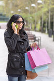 Woman talking by phone and holding shopping bags. Royalty Free Stock Photography