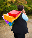 Woman talking on the phone and holding shopping bags Stock Photo