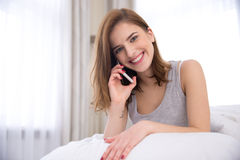 Woman talking on the phone at home Stock Images