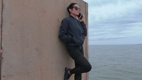 Woman talking on phone on jetty near sea stock video footage
