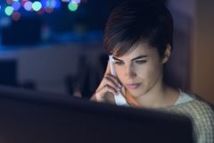 Woman talking on the phone late at night stock photo