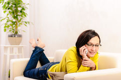 Woman talking phone living room Stock Images