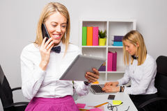 Woman talking on the phone and looking tablet. Woman talking on the phone and looking at portable tablet in office Stock Image