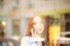 Woman talking on the phone and looking in window Stock Photo