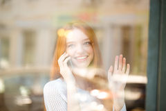 Woman talking on the phone and looking at window Royalty Free Stock Photography