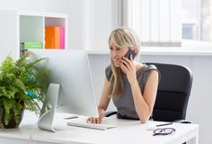 Woman talking on phone in the office Stock Image
