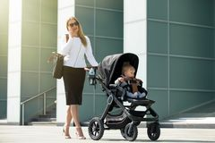 Woman talking on the phone and pushing baby stroller. Business women talking on the phone and pushing baby stroller Royalty Free Stock Photo