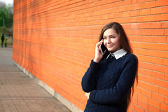 Woman talking on the phone on a red wall Stock Image