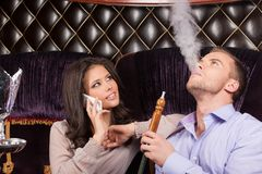Woman talking on phone and resting in Arabic cafe. Man and women smoking hookah and looking Royalty Free Stock Photos