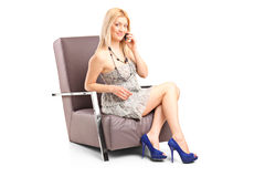 Woman talking on phone seated in an armchair Royalty Free Stock Photo