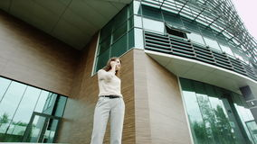 Woman talking on a phone. Serious woman talking on a phone standing near the modern building stock video