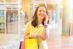 Woman talking on the phone while shopping Royalty Free Stock Photography