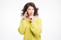 Woman talking on the phone and showing finger over lips Royalty Free Stock Photography