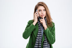 Woman talking on the phone and showing finger over lips Stock Images