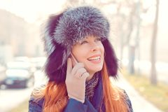Woman talking at phone smiling hat outdoor in winter royalty free stock images
