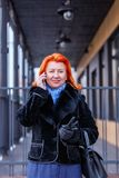 A woman is talking on the phone in the street on a blurred background. Front view stock images
