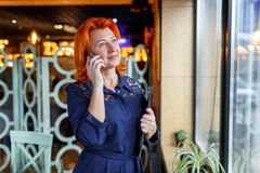 A woman is talking on the phone with a tablet in her hand at the window in a cafe with a tiring eye. A woman in age, red-haired, in a blue dress speaks on the Stock Image