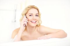 Woman talking on phone when taking a bath Stock Photos