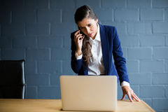 Woman talking on phone while using laptop in office Stock Photography