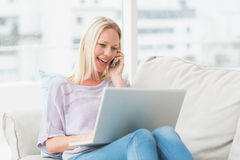 Woman talking on phone while using laptop on sofa Stock Image