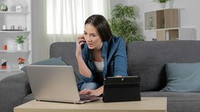 Woman talking on phone using multiple devices. Serious woman talking on phone using multiple devices at home stock footage