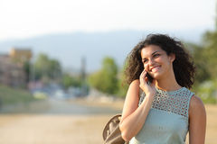 Woman talking on the phone walking in a park Stock Image