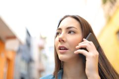 Woman talking on phone while is walking in the street stock photos
