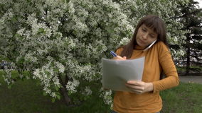 Woman talking on the phone working with documents next to blooming apple trees. A young woman in a yellow turtleneck speaks on the phone and works with stock video