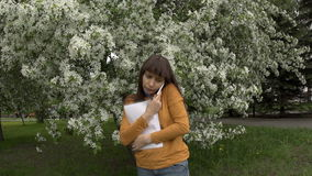 Woman talking on the phone working with documents next to blooming apple trees. A young woman in a yellow turtleneck speaks on the phone and works with stock footage