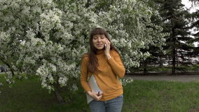 Woman talking on the phone working with documents next to blooming apple trees. stock video
