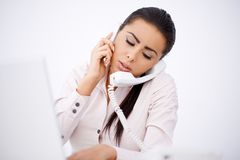 Woman talking by phones simultaneously. Overworked woman talking by cell phone and telephone simultaneously Royalty Free Stock Photography