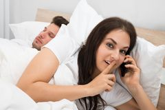 Woman talking privately on cellphone. While Her Husband Sleeping On Bed Stock Images
