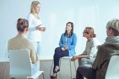 Woman talking about problems during meeting of support group with psychotherapist royalty free stock image
