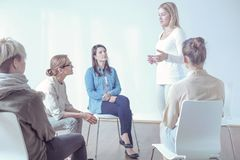Woman talking about problems to young people during therapy with psychotherapist stock images