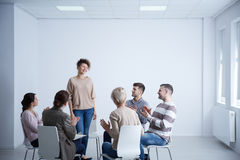 Woman talking during psychotherapy. Happy women talking in front of group during psychotherapy Stock Image