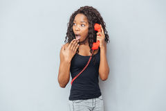 Woman talking on retro phone tube and looking away Stock Photography